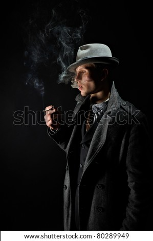 Contrast tinted in the old-style portrait of a man in a stylish elegant business suits, smoking cigarettes - stock photo