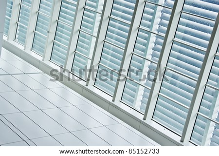 Contrast window panels with blinds beside tiled pathway - stock photo
