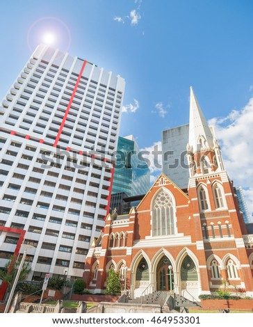 Contrasting architecural styles modern commercial skyscrapers surround traditional Albert Street Uniting church in Brisbane city Australia
