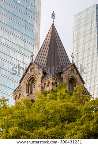 Contrasting Toronto Architecture: Vintage architecture buildings at the University of Toronto.  The slanted brown roof peeks up over a tree, and two skyscrapers can be seen in the background. - stock photo