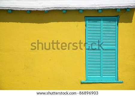Contrasting window shutters against the interesting texture of a stucco wall of a traditional Bermuda cottage. - stock photo