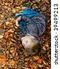 Contrasty image of child laying in Autumn leaves. - stock photo