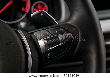 Control buttons on steering wheel. Modern car interior detail.