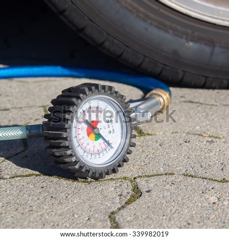 Control of the tire inflation pressure of a car, scale of a compressor - stock photo