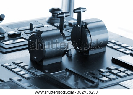 Control panel of industrial cargo ship, closeup photo with selective focus and vintage blue tonal correction filter effect, old style - stock photo