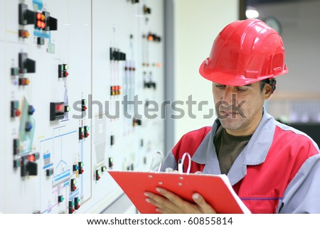 Control Room Engineer. Power plant control panel. Engineer standing in front of the control panel in the control room and writes the results of measurements. - stock photo