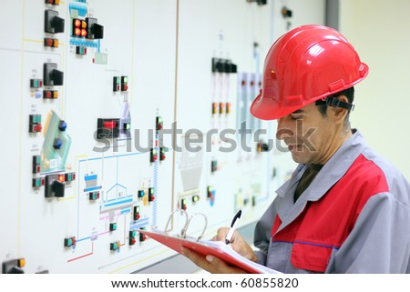 Control Room Engineer. Power Plant Control Panel. Engineer standing in front of the control panel in the control room and write the results of the measurements. - stock photo