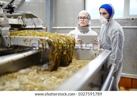 Control seafood factory staff in uniform standing by working industrial machine