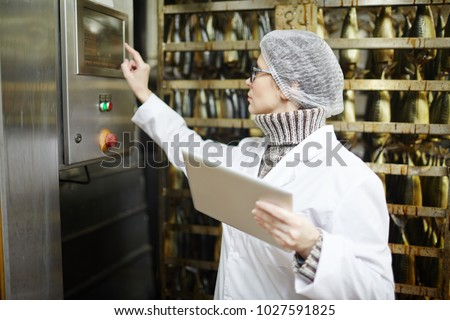 Control staff of fish factory choosing working regime of smoking machine
