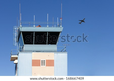Control tower at municipal airport. Upper part of blue and white building. Rooftop antennas. Silhouette of airplane in background. Clear blue sky. Horizontal photo.  - stock photo