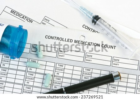 Controlled medication form with pen and prescription pills. - stock photo