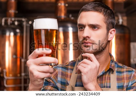 Controlling beer quality. Thoughtful young male brewer in apron holding glass with beer and looking at it while standing in front of metal containers - stock photo