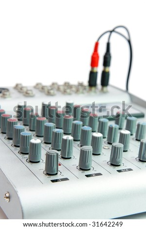 Controls of small sound mixer console with attached plug isolated - stock photo