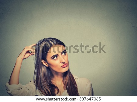 Contused thinking woman bewildered scratching her head seeks a solution isolated on gray wall background. Young woman looking up - stock photo