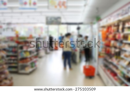 convenience store cashier with customers blur background - stock photo