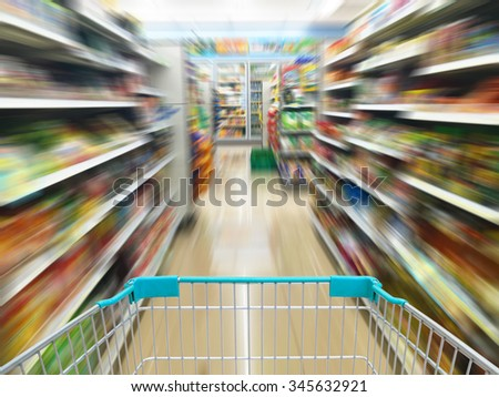 convenience store shelves with shopping cart, motion blur - stock photo