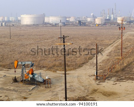 Conventional energy is represented by an oil well pumping unit in the foreground and a refinery in the background - stock photo