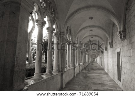 Converging lines of historic, stone cloister of  franciscan monastery in Dubrovnik, Croatia,black and white - stock photo