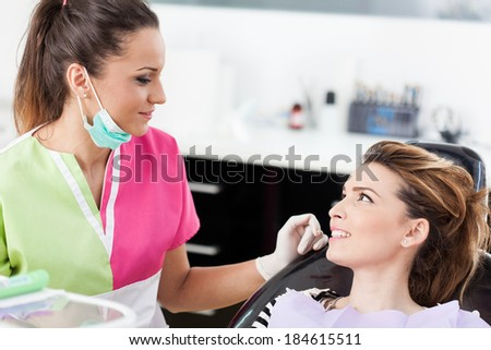 Conversation between dentist and patient with the dentist explaining the process of dental treatment - stock photo