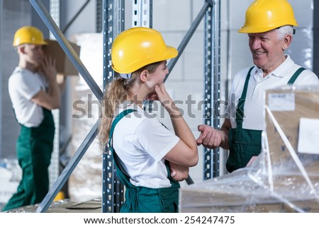 Conversation between young woman and her older colleague in warehouse - stock photo