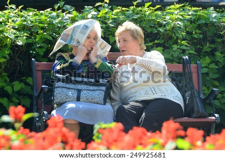 Conversation.  Two old ladies seating on the bench in the garden and talking. Russia, Saint-Petersburg, Vladimirskaya square, 08-06-2013. - stock photo
