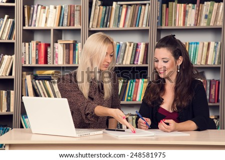 Conversation women office. Two young businesswomen having a meeting in the office sitting at a desk having a discussion with focus. Two girls students discuss course material. Work on the computer. - stock photo