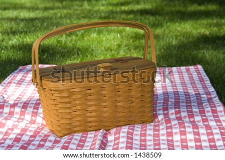 Converted from RAW not sharpened. Picnic basket sitting on red and white checked table cloth. - stock photo