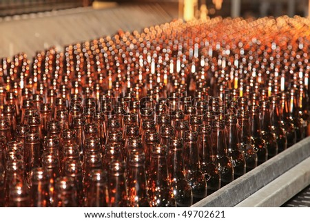 Conveyer line with many beer bottles - stock photo