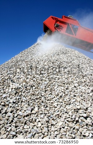 Conveyor and pile of quarry stone for building sorted according to size - stock photo