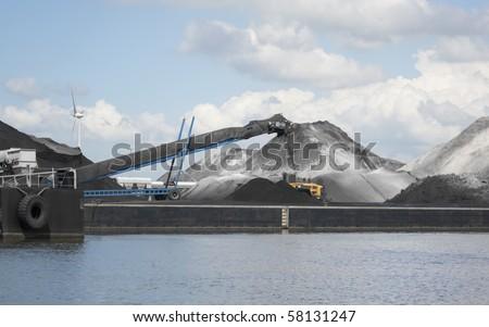 Conveyor belt processing stockpiles of bulk cargo in port - stock photo