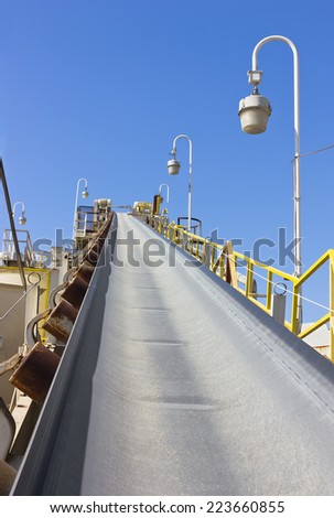 Conveyor belt sits empty at a cement factory. - stock photo