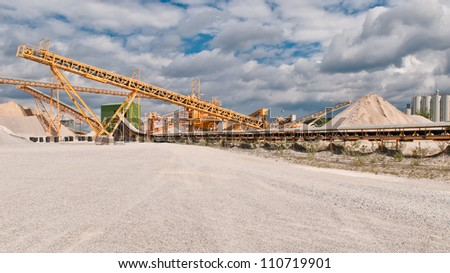 Conveyor on site at gravel pit in front of blue sky - stock photo