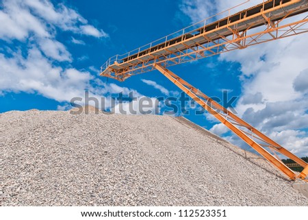 Conveyor on site at gravel pit in front of blue sky