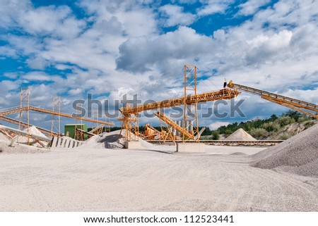 Conveyor on site at gravel pit in front of blue sky with clouds
