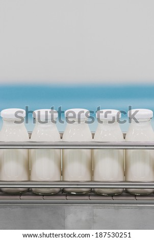 Conveyor with glass bottles filled with milk products - stock photo