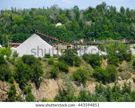 conveyor with piles of gravel granite quarry - stock photo