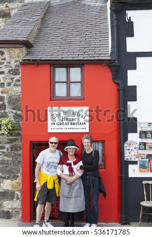 Conwy, North Wales UK - May 18 2014 Tourists pose for photographs with woman in traditional Welsh costume outside the smallest house in Great Britain.