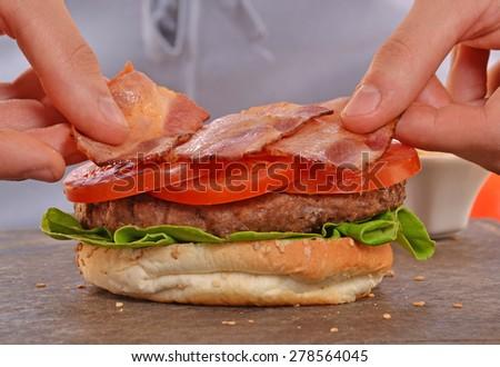 Cook adding bacon on hamburger.Making and preparing hamburger. - stock photo