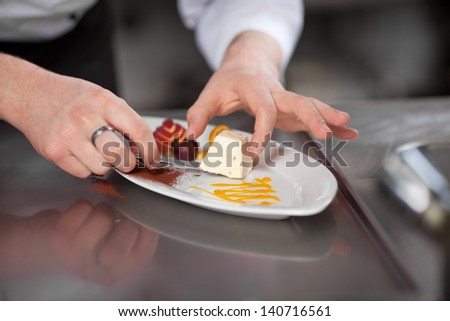 cook arranging the dessert on plate in kitchen