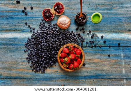 Cook bakery makes delicious dessert of strawberries blueberries, fresh bun smeared with jam and lies next to the table - stock photo