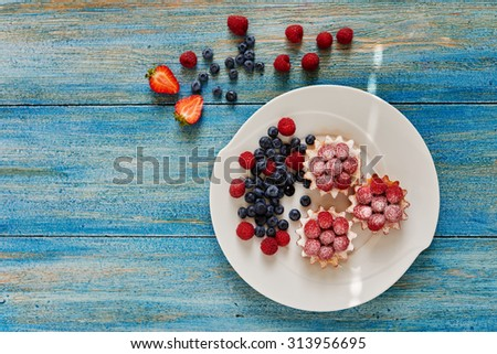 Cook cakes served on a white plate, basket of unleavened dough with raspberry jam and fresh raspberries sprinkled icing sugar, strawberries on a plate next to raspberries and blueberries - stock photo