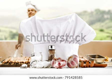 Cook chef hat on desk and man with grill at spring time. Free space for your decoration.