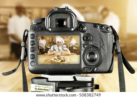 Cook chef in kitchen and big black camera