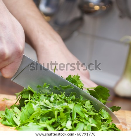 Cook chops fresh parsley with a knife - stock photo