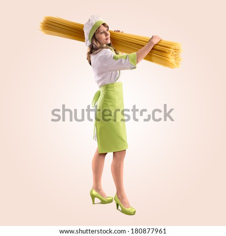 cook girl with large delicious spaghetti on a beige background - stock photo
