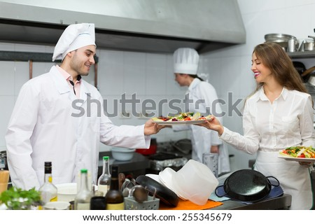 Cook gives to positive waitress plates with prepared food - stock photo