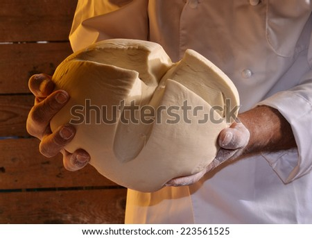 Cook hands holding a dough ball - stock photo