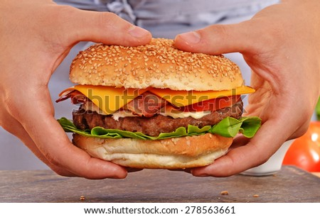 Cook hands holding and preparing hamburger. - stock photo