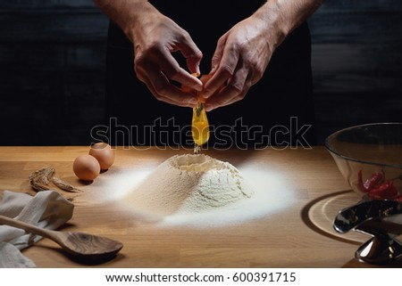 Cook hands kneading dough, cracking an egg in flour. Low key shot, close up on hands, some ingredients around on table.