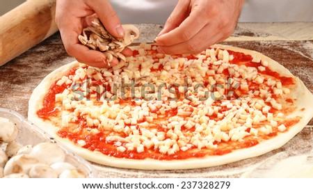Cook hands preparing pizza, adding mozzarella cheese. - stock photo